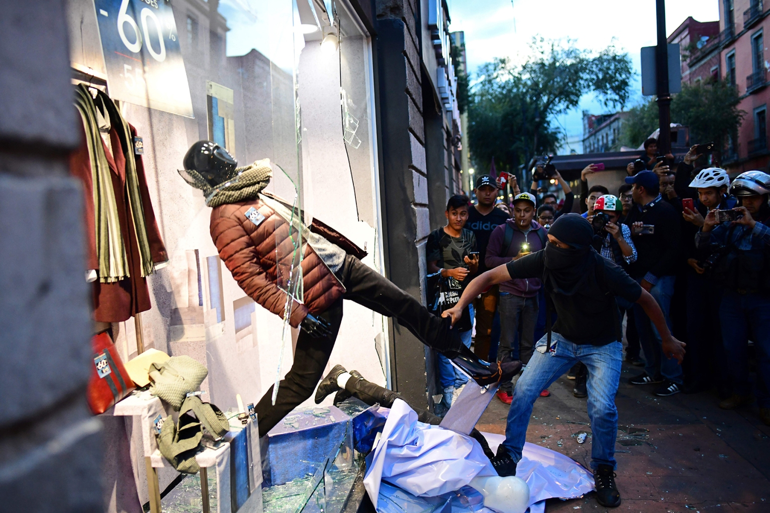 Hooded demonstrators vandalize a shop window in Mexico City on the 50th anniversary of the 1968 Tlatelolco student massacre on Oct. 2. Mexican troops opened fire on student demonstrators, killing hundreds just days before Mexico City hosted the 1968 Olympics—one of the darkest episodes in a year of global turbulence. RONALDO SCHEMIDT/AFP/Getty Images