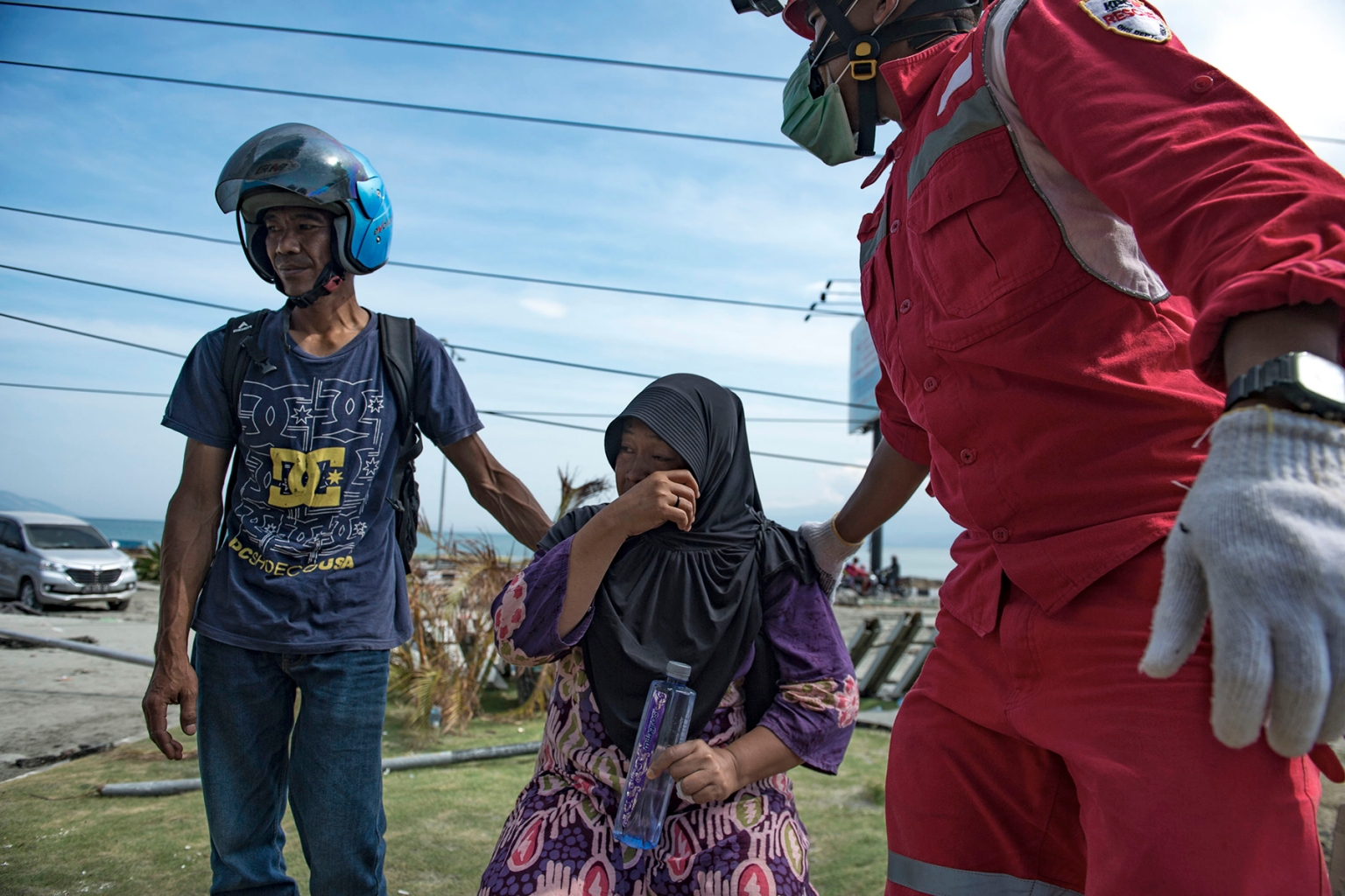 A member of a search-and-rescue team tries to calm Hadija, an Indonesian woman who is awaiting news on her brother outside the badly damaged Mercure hotel in Palu in Central Sulawesi on Oct. 4 after the earthquake and tsunami there. Bay Ismoyo/AFP/Getty Images