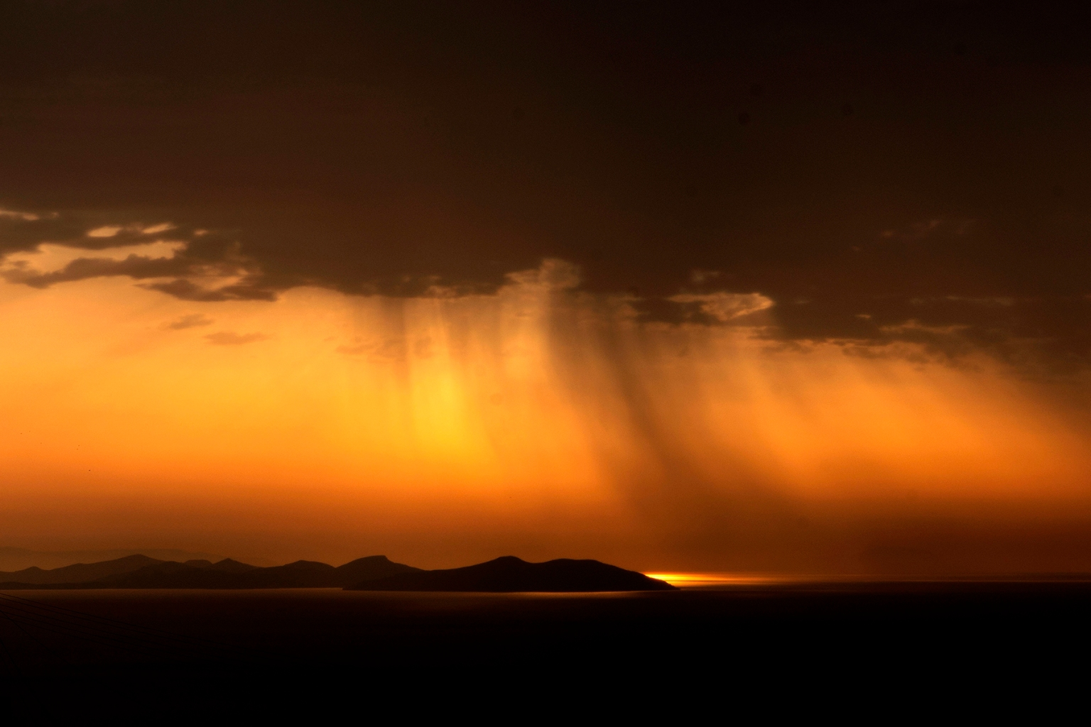The sun rises behind a bank of clouds on the Greek island of Sifnos on Oct. 4. LOUISA GOULIAMAKI/AFP/Getty Images