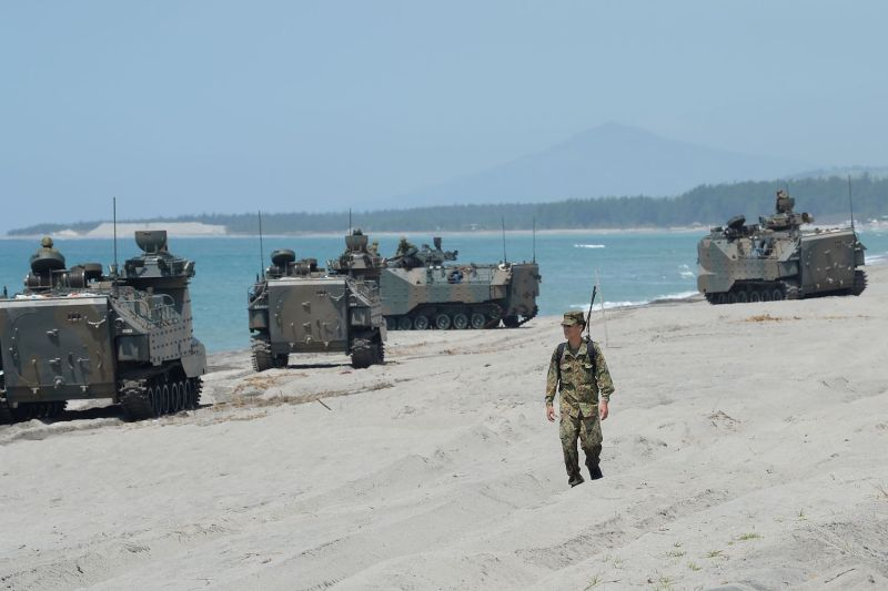 A Japanese soldier walks past amphibious assault vehicles during an amphibious landing exercise at the beach of the navy training center in Zambales province, north of Manila, as a part of a joint military exercise with the United States and the Philippines on Oct. 6. (Ted Aljibe/AFP/Getty Images)