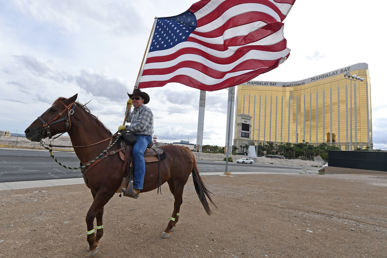 Rafael Sarabia holds an American flag as he rides his horse across from the Mandalay Bay Resort and Casino in Las Vegas, Nevada, as a tribute to the 58 people killed in last year's mass shooting at the site on Oct. 1. Ethan Miller/Getty Images