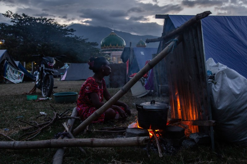 A woman cooks beside her tent at a temporary shelter in Palu, Indonesia, on Oct. 9. (Ulet Ifansasti/Getty Images)