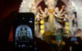 "Indians take pictures of a Durga idol inside a makeshift ""pandal"" structure in Kolkata on Oct. 16. (DIBYANGSHU SARKAR/AFP/Getty Images)"