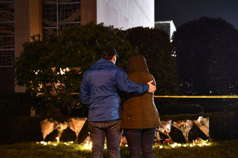Lorea Stallard and her husband, Kyle Parker, stand in front of flowers and candles placed outside the Tree of Life synagogue after a shooting there left 11 dead in Pittsburgh on Oct. 27. (Brendan Smialowski/AFP/Getty Images)