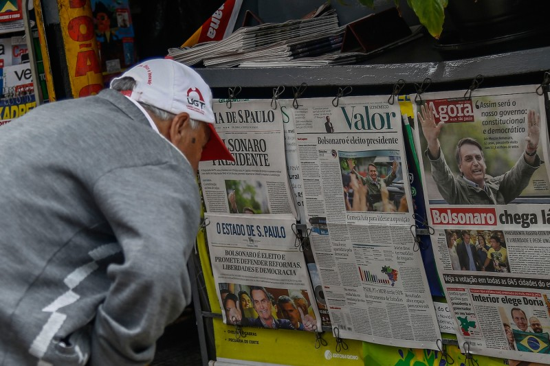 A man reads newspaper headlines announcing Jair Bolsonaro's victory in the Brazil's presidential election in São Paulo on Oct. 29. (Miguel Schincariol/AFP/Getty Images)