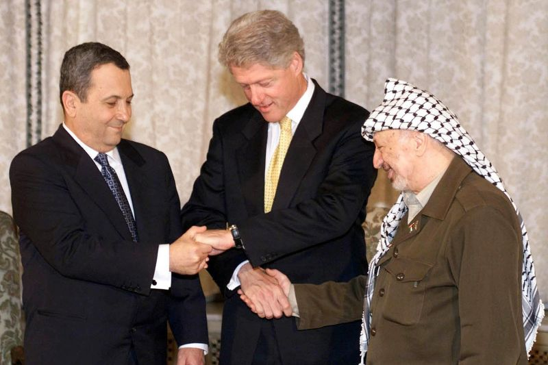 U.S. President Bill Clinton, Israeli Prime Minister Ehud Barak, and Palestinian leader Yasser Arafat shake hands before a meeting in Oslo to discuss the Mideast peace process on Nov. 2, 1999. (Lise Aserud/AFP/Getty Images)