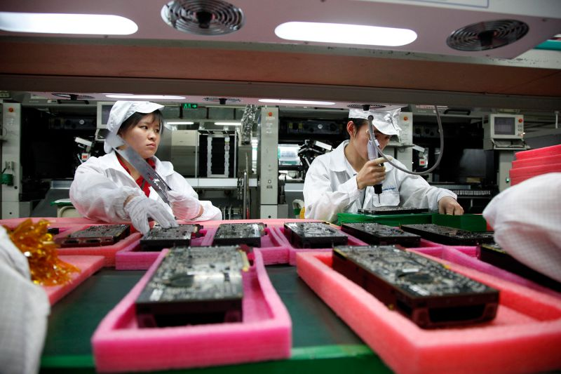 Employees work on the assembly line at a Foxconn plant in Shenzhen, China, on May 26, 2010. China is a parts supplier for many high-tech companies around the world, including Apple. (In Pictures Ltd./Corbis via Getty Images)