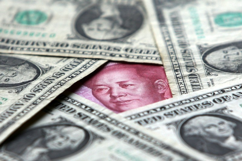 Dollar and yuan notes are seen at a bank in Beijing on May 15, 2006. (China Photos/Getty Images)