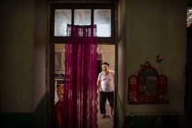 "A Uighur man and his granddaughter are seen in their home after a meal during the Corban Festival, known to Muslims worldwide as Eid al-Adha or ""feast of the sacrifice,"" in China's far western Xinjiang province on Sept. 12, 2016. (Kevin Frayer/Getty Images)"