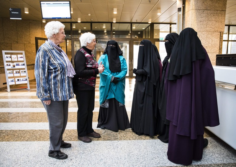 Two women stand next to women wearing the niqab in the Hague, the Netherlands, on Nov. 23, 2016. (STR/AFP/Getty Images)