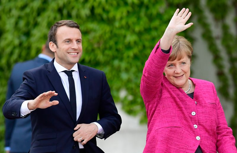 German Chancellor Angela Merkel and French President Emmanuel Macron wave to the crowds during a welcoming ceremony at the chancellery in Berlin on May 15, 2017. (Tobias Schwarz/AFP/Getty Images)