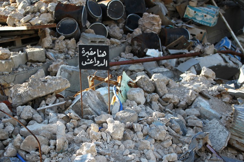 "A sign that reads ""Here is a cemetery of the Islamic State group"" sticks out from a pile of rubble in the old city of Mosul on Jan. 9. (Ahmad al-Rubaye/AFP/Getty Images)"
