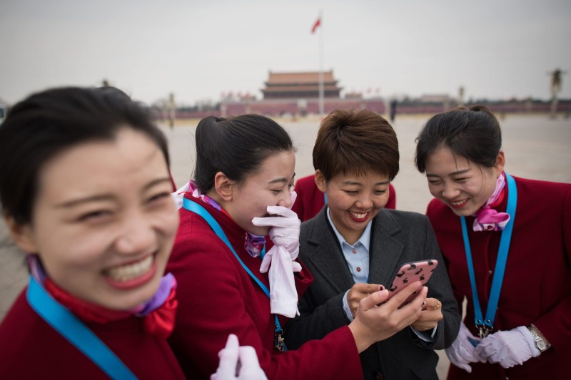 Hostesses laugh as they look at photos on their phones during the National People's Congress at the the Great Hall of the People in Beijing on March 11. (Nicolas Asfouri/AFP/Getty Images)