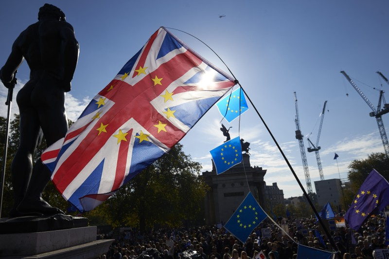 Demonstrators wave a British flag with European Union stars and European Union flags as they take part in a march calling for a People's Vote on the final Brexit deal, in central London on Oct. 20.