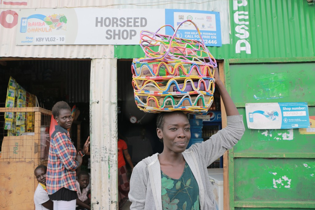 Lillian Ochan, a 23-year-old refugee from Ethiopia, buys food items using bamba chakula cash from a shop in Kenya's Kalobeyei settlement, village 2, in Kakuma on May 21. (World Food Programme/Martin Karimi)