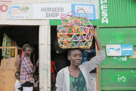 Lillian Ochan, a 23-year-old refugee from Ethiopia, buys food items using bamba chakula cash from a shop in Kenya's Kalobeyei settlement, village 2, in Kakuma on May 21. (World Food Programme/Martin Karimi)