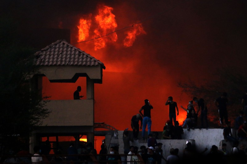 Iraqi protesters watch an official building in flames as they demonstrate against the government and the lack of basic services in Basra on Sept. 6. (Haidar Hohammed Ali/AFP/Getty Images)