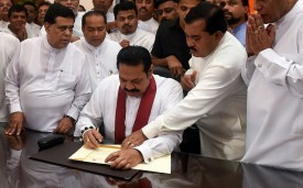 Sri Lanka's newly appointed prime minister, Mahinda Rajapaksa (center), signs a document during a ceremony to assume duties at the prime minister's office in Colombo on Oct. 29. (Ishara S. Kodikara/AFP/Getty Images)