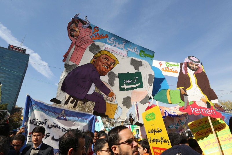 Iranian protesters carry placards that mock U.S. President Donald Trump and Saudi Arabia's King Salman and Crown Prince Mohammed bin Salman during a demonstration outside the former U.S. Embassy in Tehran on Nov. 4. (Atta Kenare/AFP/Getty Images)