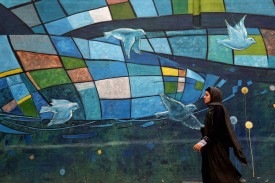 An Iranian woman walks past a mural in Tehran on Nov. 5. (Atta Kenare/AFP/Getty Images)
