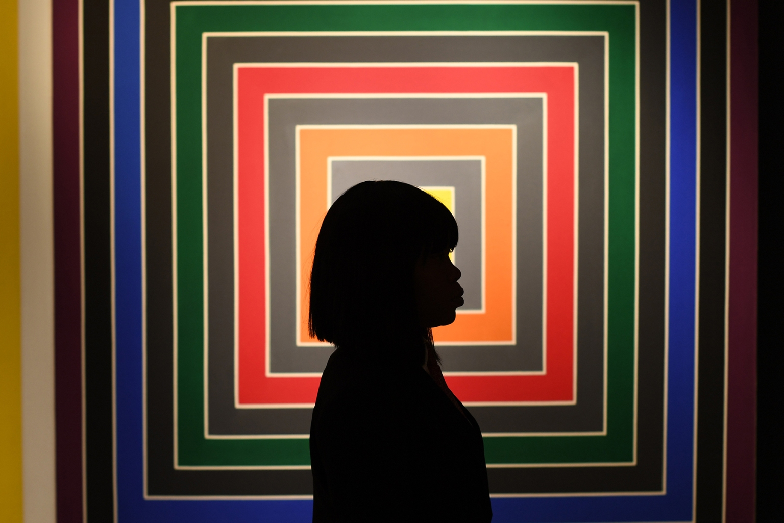 "A visitor walks past Frank Stella's ""Gray Scramble"" during a press preview at Christie's New York  ahead of their Post-War and Contemporary Art Evening Sale on Nov. 5. TIMOTHY A. CLARY/AFP/Getty Images"