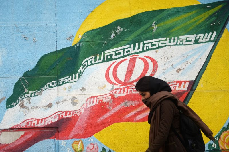 A woman walks past a mural in Tehran on Nov. 6.(Fatemeh Bahrami/Anadolu Agency/Getty Images)