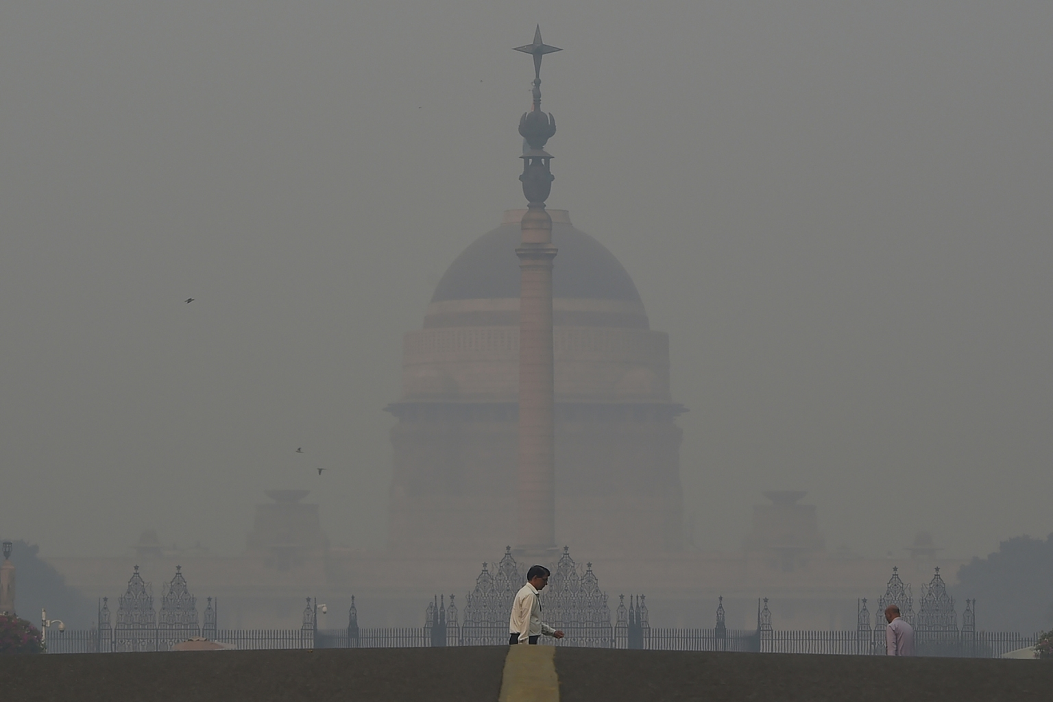 A pedestrian crosses a road near the Indian president's house amid heavy smog in New Delhi on Nov. 8. Air pollution in New Delhi hit hazardous levels after a night of Diwali fireworks, despite Supreme Court efforts to curb partying that fuels the Indian capital's toxic smog problem. MONEY SHARMA/AFP/Getty Images