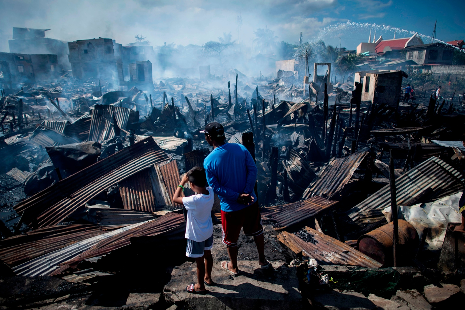 Residents look at destroyed houses after a fire engulfed a Navotas slum along Manila Bay in the Philippines on Nov. 8. Some 150 families were affected by the fire. NOEL CELIS/AFP/Getty Images