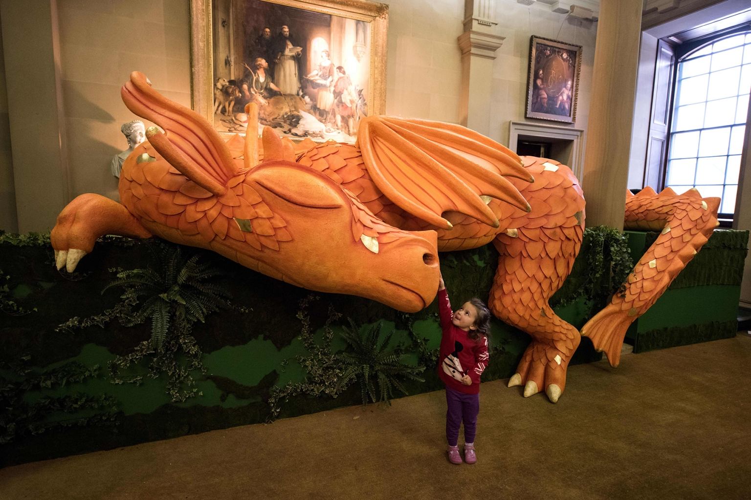 A 3-year-old girl plays with a model of a sleeping dragon in the hall of Chatsworth House which has been decorated for their Christmas season in various fairy tale scenes on the theme of 'Once Upon a Time', during a photocall at Chatsworth House near Bakewell, northern England on November 8, 2018. - Various rooms in Chatsworth, the residence of Britian's Duke and Duchess of Devonshire, which is open to the public, are decorated every year for the festive season. (Photo by OLI SCARFF / AFP)        (Photo credit should read OLI SCARFF/AFP/Getty Images)