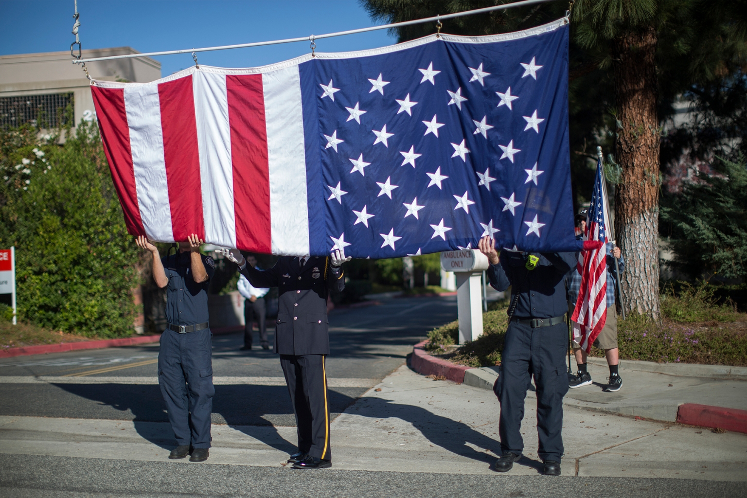Firefighters raise a flag to hang over the procession carrying the body of Ventura County Sheriff Sgt. Ron Helus, who was killed in the mass shooting at the Borderline Bar and Grill in Thousand Oaks, California, on Nov. 8, 2018. (David McNew/Getty Images)