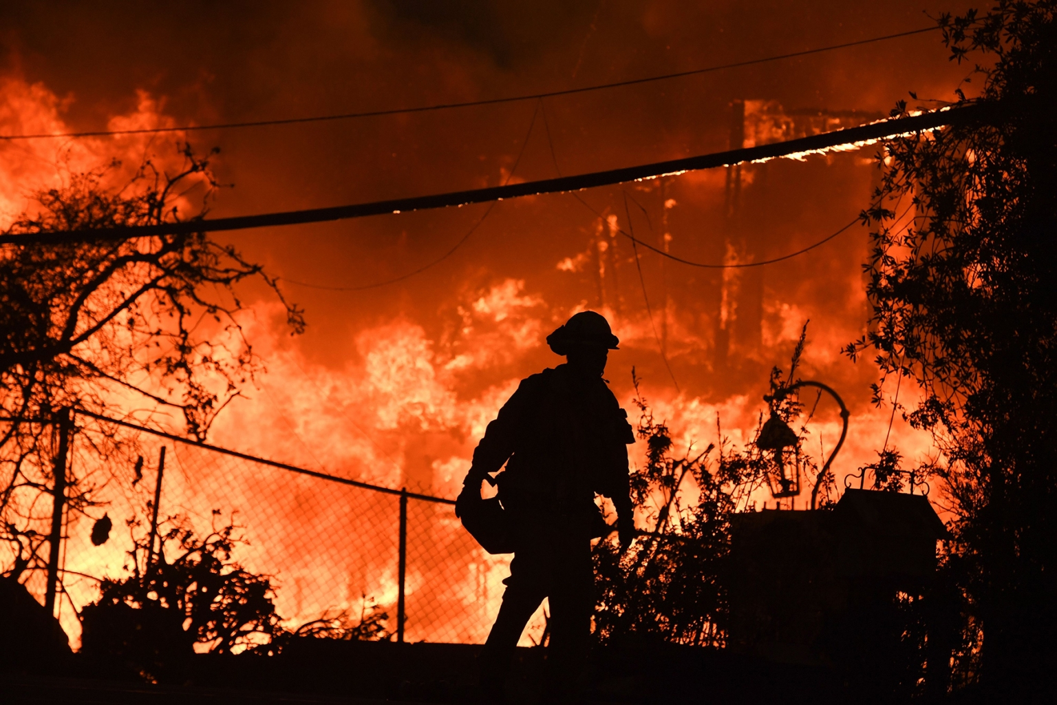 A firefighter is silhouetted by a burning home along Pacific Coast Highway during the Woolsey Fire in Malibu, California, on Nov. 9. ROBYN BECK/AFP/Getty Images