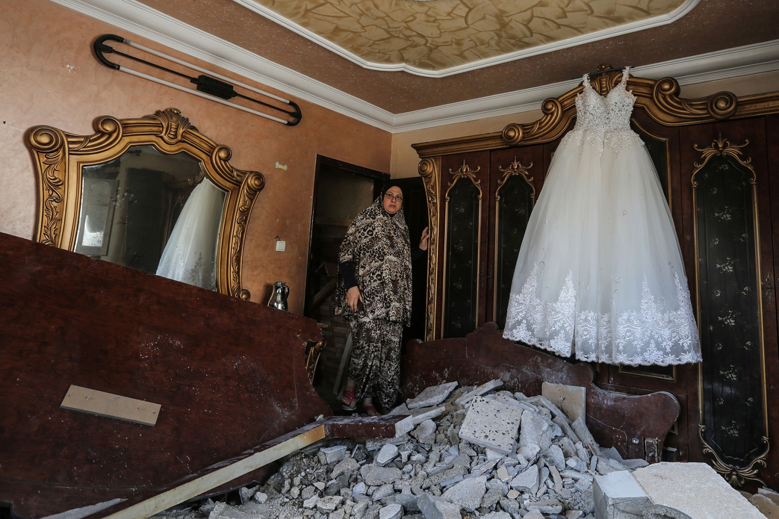 A Palestinian woman walks into a room damaged by an Israeli airstrike earlier this week in the Gaza Strip on Nov. 14. A ceasefire held began after the worst escalation between Israel and Gaza militants since a 2014 war, but the situation remained volatile and the deal provoked sharp disagreement within the Israeli government. MAHMUD HAMS/AFP/Getty Images