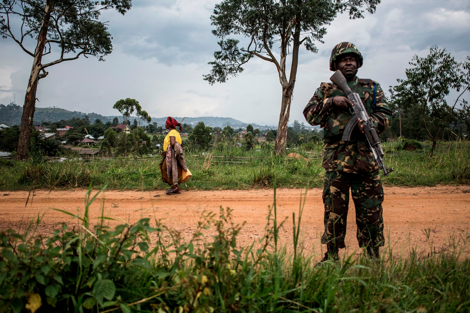 A woman walks by as a Tanzanian soldier from the United Nations Organization Stabilization Mission in the Democratic Republic of the Congo patrols against Ugandan Allied Democratic Force rebels in Beni on Nov. 13. For the past four years, the Beni area has been under seige from the an Islamist armed group that has killed hundreds of people. JOHN WESSELS/AFP/Getty Images