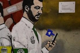 "A new mural by Italian street artist Tvboy, entitled ""La Guerra dei Socials"" (The War of Social Media), depicting Matteo Salvini in Milan on Nov. 14. (Miguel Medina/AFP/Getty Images)"