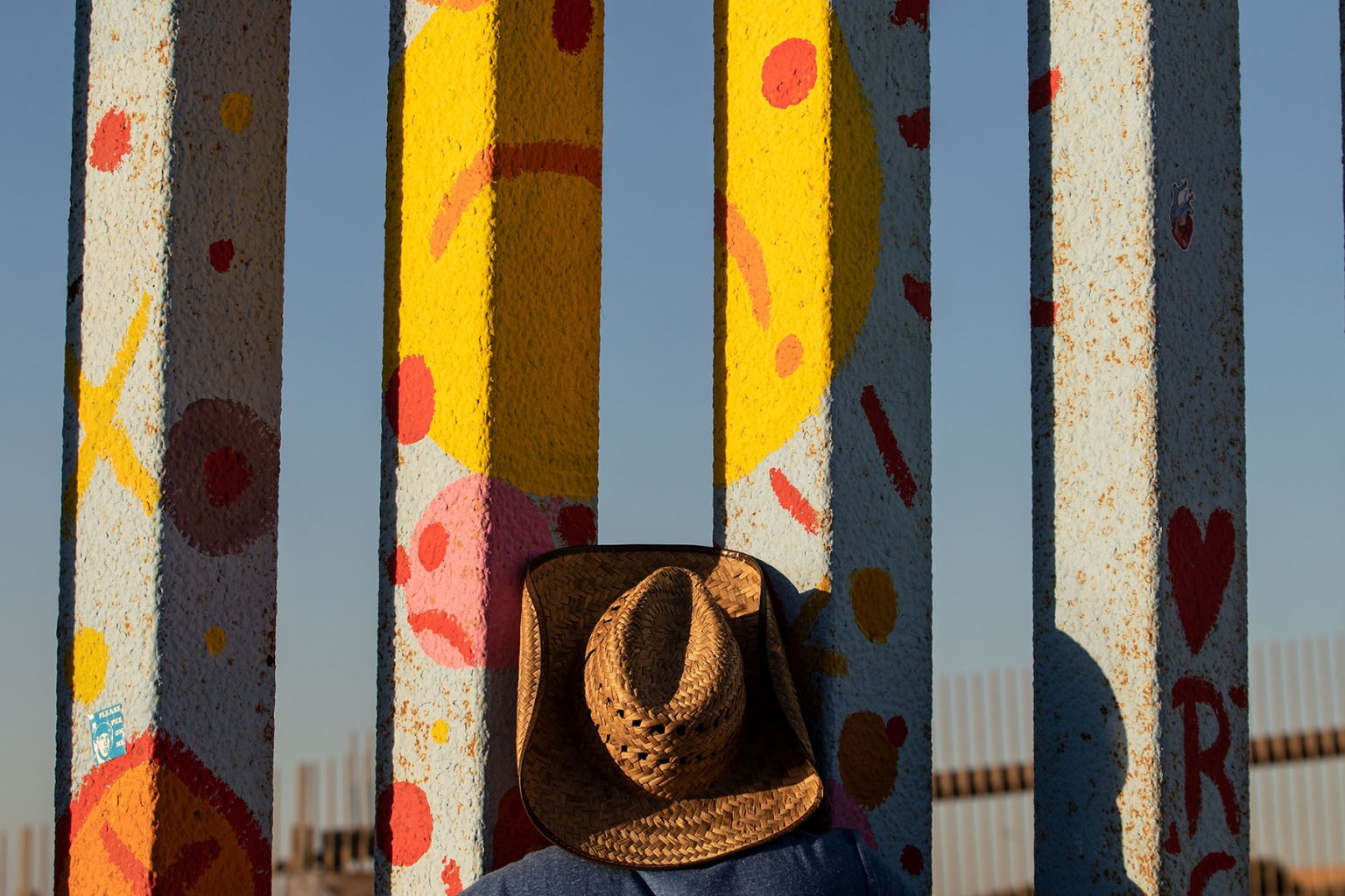 A Central American migrant looks through the U.S.-Mexico border fence in Playas de Tijuana, Mexico, on Nov. 14. GUILLERMO ARIAS/AFP/Getty Images