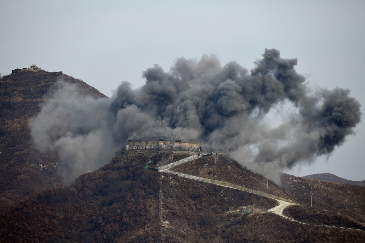 A South Korean guard post explodes as it is dismantled in the Demilitarized Zone dividing the two Koreas in Cheorwon on Nov. 15. The two Koreas began destroying 20 guard posts along their heavily fortified frontier on under a plan to reduce tensions on the border. JUNG YEON-JE/AFP/Getty Images