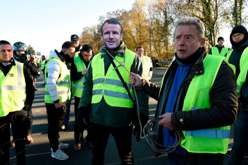 A man wears a mask of French President Emmanuel Macron during a protest against rising fuel prices on Nov. 17 in Haulchin, France. (Francois Lo Presti/AFP/Getty Images)