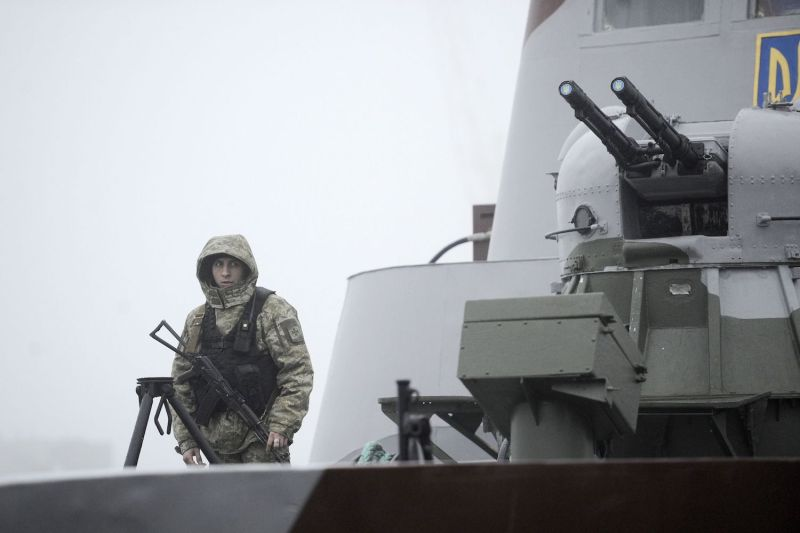A Ukrainian soldier patrols a boat moored in Mariupol, Ukraine, on the Sea of Azov on Nov. 27. (Sega Volskii/AFP/Getty Images)