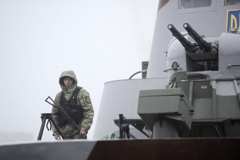 A Ukrainian soldier patrols a boat moored in Mariupol, Ukraine, on the Sea of Azov on Nov. 27. (Sega Volskii/AFP/Getty Images)