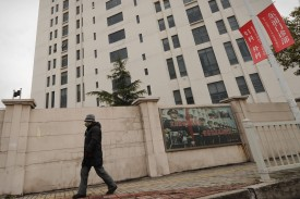 A person walks past a 12-story building alleged in a report on Feb. 19, 2013, by the internet security firm Mandiant as the home of a Chinese military-led hacking group after the firm reportedly traced a host of cyberattacks to the building in Shanghai's northern suburb of Gaoqiao. (Peter Parks/AFP/Getty Images)