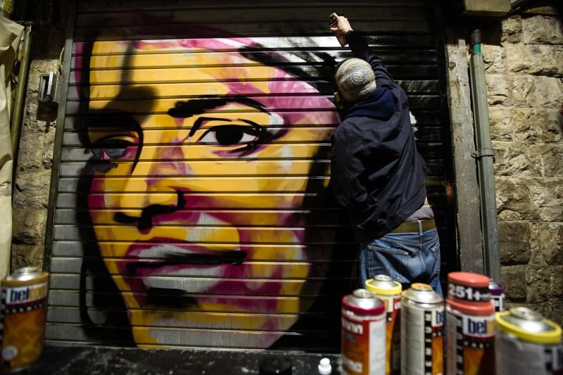 Artist Solomon Souza paints a portrait of Israeli-Arab news anchor Lucy Aharish over a closed shutter at the Mahane Yehuda Market on Feb. 24, 2016, in Jerusalem. (David Vaaknin/The Washington Post via Getty Images)