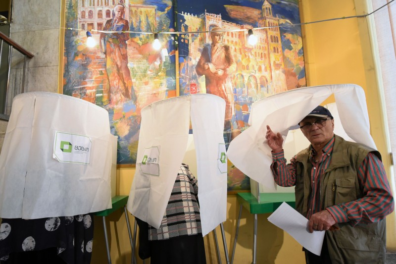 A man leaves a voting booth at a polling station during parliamentary elections in Tbilisi, Georgia, on Oct. 8, 2016. (Vano Shlamov/AFP/Getty Images)