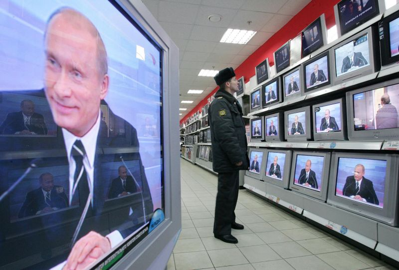 A Russian policeman looks at TV screens in a shop in Moscow on Feb. 1, 2007, during the broadcasting of Russian President Vladimir Putin's annual address to Russian and foreign media. (Denis Sinyakov/AFP/Getty)