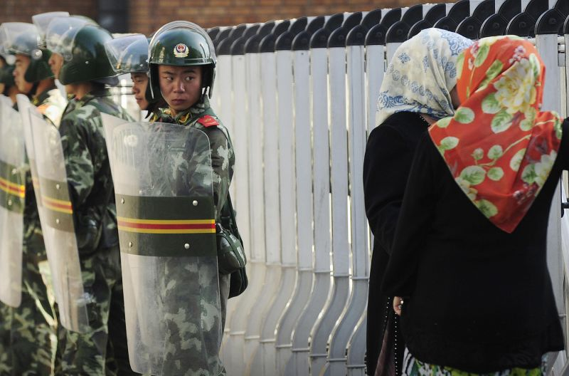Ethnic Uigur women look through a security fence as Chinese soldiers stand guard in Urumqi, in China's far west Xinjiang region, on July 9, 2009. (Peter Parks/AFP/Getty Images)