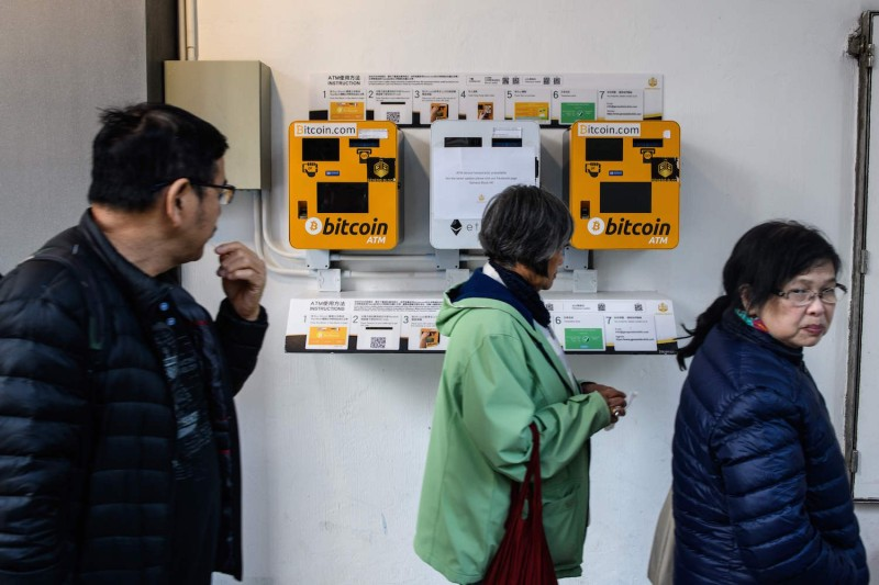 Pedestrians walk past ATMs for the digital currency bitcoin in Hong Kong on Dec. 18, 2017.   (Anthony Wallace/AFP/Getty Images)