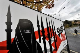 A woman walks behind a campaign posters of the far-right Swiss People's Party depicting a woman wearing a burqa against a background of a Swiss flag on Nov. 23, 2009 in Corseaux near Vevey. (Fabrice Cofrini/AFP/Getty Images)