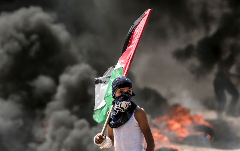 A boy holding a Palestinian  flag looks at clashes with Israeli security forces near the border between Gaza and and Israel on May 14. (Mahmud Hams/AFP/Getty Images)