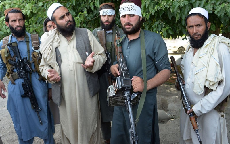 Afghan Taliban militants stand with residents as they took to the street to celebrate ceasefire on the second day of Eid in the outskirts of Jalalabad on June 16,2018. - Taliban fighters and Afghan security forces hugged and took selfies with each other in restive eastern Afghanistan on June 16, as an unprecedented ceasefire in the war-torn country held for the second day of Eid. (NOORULLAH SHIRZADA/AFP/Getty Images)
