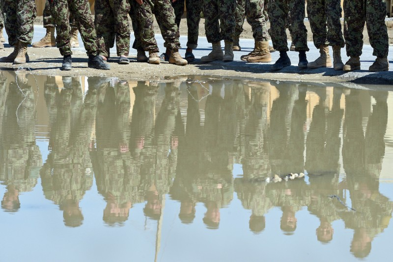 Afghanistan National Army  soldiers are reflected in the water as they stand near a dam during a ceremony on March 25, 2012.
