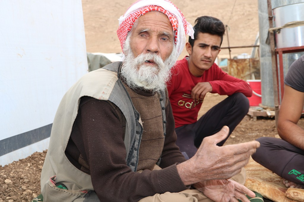 Herto Hamrash Minut, 74, sits outside his house on Sinjar Mountain, where he lives with his two wives and 12 children. Four years ago, he was kidnapped and tortured by the Islamic State for eight months. (Sam Mednick for Foreign Policy)